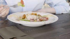 Den unga affärskvinnan äter, medan sitta på tabellen i restaurang lager videofilmer