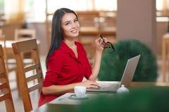 Den unga affärskvinnan använder bärbara datorn i kafé royaltyfri foto