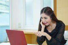 Den unga affärskvinnan förvånade att peka till bärbar datorskärmen Arkivfoton