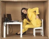 Den unga affärskvinnan har tillbaka att smärta från en dålig kontorsstol arkivbild