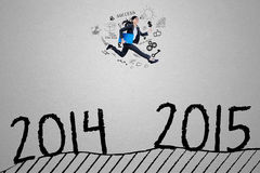 Den unga affärskvinnan hoppar ovanför numret 2014 till 2015 Royaltyfri Foto