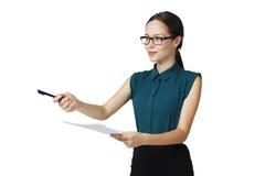 Den unga affärskvinnan i exponeringsglas ger en penna för att underteckna dokumentet Fotografering för Bildbyråer
