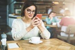 Den unga affärskvinnan i exponeringsglas och den vita tröjan sitter i kafé på tabellen och använder smartphonen som arbetar E-lär fotografering för bildbyråer