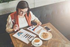 Den unga affärskvinnan i exponeringsglas och den vita tröjan sitter i kafé på tabellen som arbetar Kvinnan ser diagram, grafer Royaltyfria Bilder
