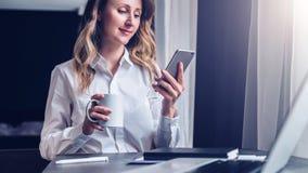 Den unga affärskvinnan i skjorta sitter i regeringsställning på tabellen framme av datoren, genom att använda smartphonen, blicka Arkivfoton