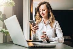Den unga affärskvinnan i skjorta sitter i regeringsställning på tabellen framme av datoren, genom att använda smartphonen, blicka Arkivbilder