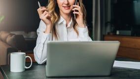Den unga affärskvinnan i skjorta sitter i regeringsställning på tabellen framme av datoren och att tala på mobiltelefonen Arkivfoton