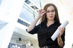 Den unga affärskvinnan justerar exponeringsglasen, rymmer papperet i hennes hand Fotografering för Bildbyråer