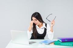 Den unga affärskvinnan känner sig det trötta och hållande huvudet på arbetsskrivbordet som isoleras på vit bakgrund royaltyfria bilder