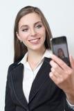Den unga affärskvinnan ler, medan ta en selfiebild Fotografering för Bildbyråer