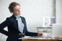 Den unga affärskvinnan med backen smärtar arkivbilder