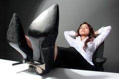 Den unga affärskvinnan med ben korsade på tabellen som vilar Arkivbilder