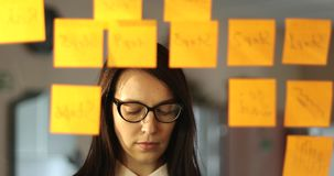Den unga affärskvinnan med exponeringsglas klibbar små klistermärkear på exponeringsglaset i kontoret lager videofilmer