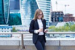 Den unga affärskvinnan med kaffe motsvarar med kunden på telefonen på gatan Arkivbild