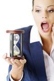 Den unga affärskvinnan med timglas - time begreppet Royaltyfria Foton