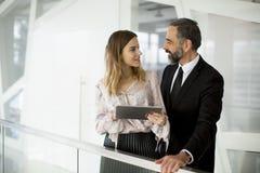 Den unga affärskvinnan och affärsmannen ser på den digitala minnestavlan och D Arkivfoton