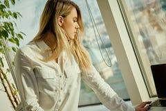 Den unga affärskvinnan ser dokument i ett ljust kontor Royaltyfri Bild