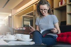 Den unga affärskvinnan sitter på soffan i hotelllobbyen, restaurangen, kafét, drinkkaffe och läser boken, tidskriften, katalog arkivfoto