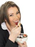 Den unga affärskvinnan som äter en bunke av sädesslag med yoghurt och, är Arkivfoton