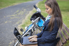 Den unga affärskvinnan som använder bärbara datorn, medan sitta på bänk på, parkerar Fotografering för Bildbyråer