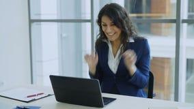 Den unga affärskvinnan som använder meddelandet för hälerit för bärbar datordatoren det bra och blir mycket upphetsad och lycklig stock video