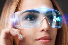 Den unga affärskvinnan som arbetar i faktiska exponeringsglas, väljer symbolen CRM på den faktiska skärmen Arkivfoto
