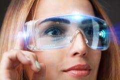 Den unga affärskvinnan som arbetar i faktiska exponeringsglas, väljer symbolsområdet på den faktiska skärmen Fotografering för Bildbyråer