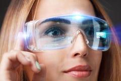 Den unga affärskvinnan som arbetar i faktiska exponeringsglas, väljer symbolsoptimizationprocessen på den faktiska skärmen Fotografering för Bildbyråer