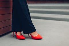Den unga affärskvinnan som bär röd höjdpunkt, heeled skor Stilfulla klassikerpumpar Closeup av kvinnligben arkivbilder