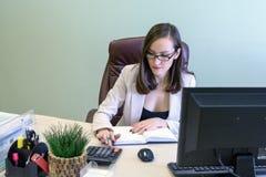 Den unga affärskvinnan som hårt arbetar över skrivbordet i studien, finansiellt anmäla för ekonomrevisor, verifierar exakthet av  Arkivfoto
