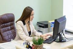 Den unga affärskvinnan som hårt arbetar över skrivbordet i studien, finansiellt anmäla för ekonomrevisor, verifierar exakthet av  Arkivbild