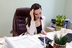 Den unga affärskvinnan som hårt arbetar över skrivbordet i studien, finansiellt anmäla för ekonomrevisor, verifierar exakthet av  Royaltyfri Fotografi