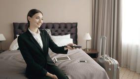 Den unga affärskvinnan som kopplar av i hotellrum och ser tv, väljer chanel med fjärrkontroll stock video