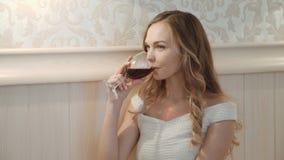 Den unga affärskvinnan som kopplar av på sängen, dricker från ett exponeringsglas av rött vin på hennes hotellsovrum på säng i ly stock video