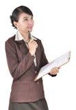 Den unga affärskvinnan tänker med att bära en mapp Royaltyfri Bild