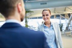 Den unga affärskvinnan välkomnar en kollega i flygplatsen arkivfoton