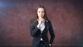Den unga affärskvinnaståenden i dräktanseende och fingret upp near hennes kanter med hyssjar tecknet, bakgrund med copyspace Arkivbilder