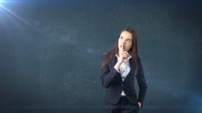 Den unga affärskvinnaståenden i dräktanseende och fingret upp near hennes kanter med hyssjar tecknet, bakgrund med copyspace Royaltyfri Foto