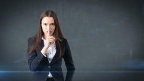 Den unga affärskvinnaståenden i dräktanseende och fingret upp near hennes kanter med hyssjar tecknet, bakgrund med copyspace Royaltyfri Fotografi