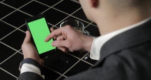 Den unga affärsmanbrukssmarthponen med greenscreen touchpaden och göra en gestslut upp i kafé Cell- grabbinnehav och att knacka l arkivfilmer