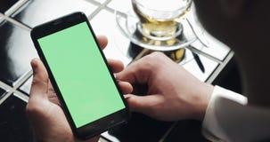 Den unga affärsmanbrukssmarthponen med greenscreen touchpaden och göra en gestslut upp i kafé Cell- grabbinnehav och att knacka l lager videofilmer