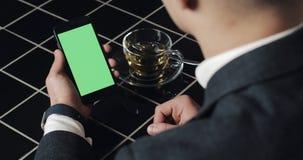 Den unga affärsmanbrukssmarthponen med greenscreen touchpaden och göra en gestslut upp i kafé Cell- grabbinnehav och att knacka l stock video