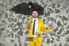 Den unga affärsmannen är mycket rik, pengarregn royaltyfria bilder