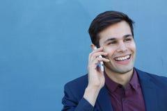Den unga affärsmannen förvånades för att motta en telefon som isolerades på blå bakgrund med kopieringsutrymme för att tillfoga t Royaltyfri Foto