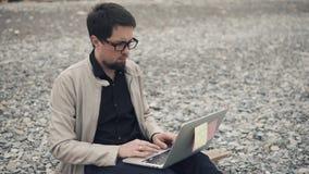 Den unga affärsmannen framkallar en start på en stenig strand genom att använda en bärbar dator lager videofilmer