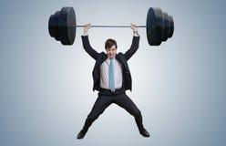 Den unga affärsmannen i dräkt lyfter tunga vikter arkivfoton