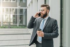 Den unga affärsmannen i dräkt och band står utomhus-, dricker kaffe och talar på hans mobiltelefon Mannen arbetar Arkivbild