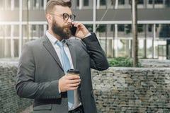 Den unga affärsmannen i dräkt och band står utomhus-, dricker kaffe och talar på hans mobiltelefon Mannen arbetar Royaltyfri Bild