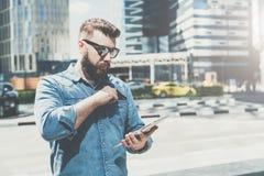 Den unga affärsmannen i solglasögon står på stadsgatan och använder minnestavladatoren, medan drar ut kreditering Royaltyfria Bilder