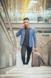 Den unga affärsmannen klättrar trappa i flygplatsen som talar vid t royaltyfria foton